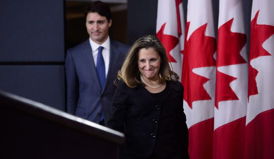 Prime Minister Justin Trudeau and Minister of Foreign Affairs Chrystia Freeland arrive to hold a press conference regarding the United States Mexico Canada Agreement (USMCA) at the National Press Theatre, in Ottawa on Monday, Oct. 1, 2018. (Sean Kilpatrick/The Canadian Press via AP)