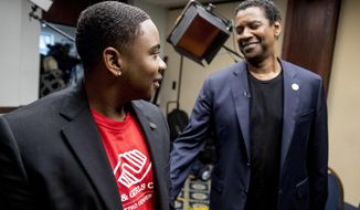 FILE - In this Sept. 26, 2018 file photo, actor Denzel Washington, right, speaks with Malachi Haynes following an interview with Fox News Anchor Chris Wallace at the National Press Club in Washington.  The Boys & Girls Clubs of America named Haynes the Southwest Youth of the Year. The organization, which began in 1860, offers a positive alternative to children than roaming the street. Washington, who joined when he was 5, is a national spokesman for the organization. (AP Photo/Andrew Harnik, File)