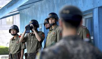 FILE - In this Monday, Aug. 13, 2018, file photo, South Korean, right, and North Korean army soldiers stand guard at the border village of Panmunjom in the Demilitarized Zone, South Korea. A South Korean government delegation has flown to North Korea to jointly celebrate the anniversary of a 2007 inter-Korean summit and potentially engage in further peace talks. (Korea Pool/Yonhap via AP, File)