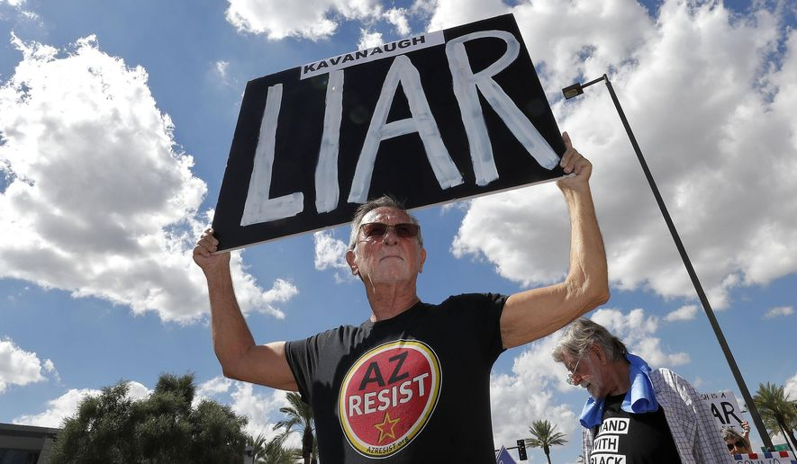 Terry Swann protests against U.S. Supreme Court nominee Brett Kavanaugh outside the office of U.S. Sen. Jeff Flake, R-Ariz., Thursday, Oct. 4, 2018, in Phoenix. (AP Photo/Matt York) ** FILE **