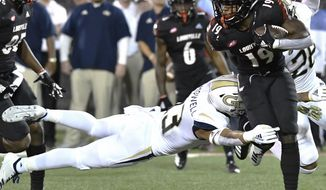 Georgia Tech defensive back Avery Showell (13) attempts a diving tackle on Louisville running back Hassan Hall (19) during the second half of an NCAA college football game, Friday, Oct. 5, 2018, in Louisville, Ky. Georgia Tech won 66-31. (AP Photo/Timothy D. Easley)