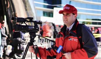 """In this Thursday, Oct. 4, 2018 photo, KTTC-TV multimedia journalist James Bunner wears a """"Make America Great Again"""" hat while interviewing people waiting to see President Donald Trump in Rochester, Minn. News Director Noel Sederstrom says the station does not allow staff members to cover stories while wearing apparel from political campaigns. Sederstrom says Bunner was fired. (Mark Vancleave/Star Tribune via AP)"""