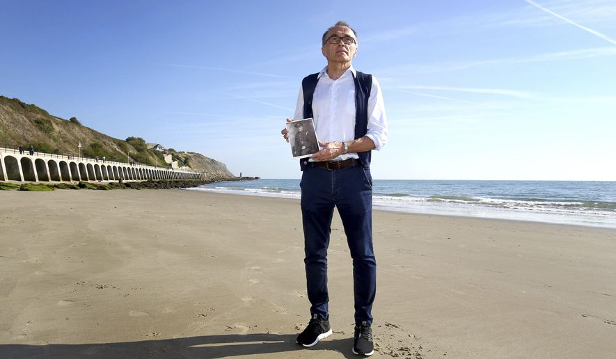 British filmmaker  Danny Boyle holds a photograph of Private Walter Bleakley, who lived on the same street where Boyle went to school, as he announces plans for his Armistice Day commission for 14-18 NOW, the UK's arts programme for the First World War centenary, on the beach, in Folkestone, England, Friday Oct. 5, 2018. Boyle is urging thousands of people to gather on British beaches and make silhouettes in the sand on Nov. 11 to mark 100 years since the end of World War I. Artists will also create giant portraits of people killed in the war, which will be washed away by the incoming tide. The commemoration caps four years of cultural activities marking the centenary of the 1914-18 conflict, in which 20 million people died. (Gareth Fuller/PA via AP)