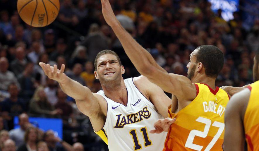 In this Tuesday, April 3, 2018 file photo, Los Angeles Lakers center Brook Lopez (11) lays the ball up as Utah Jazz center Rudy Gobert (27) defends during the first half of an NBA basketball game in Salt Lake City.  Lopez, the Milwaukee Bucks' key free agent acquisition is a big man who could have an impact on the floor from the perimeter. (AP Photo/Rick Bowmer, File)