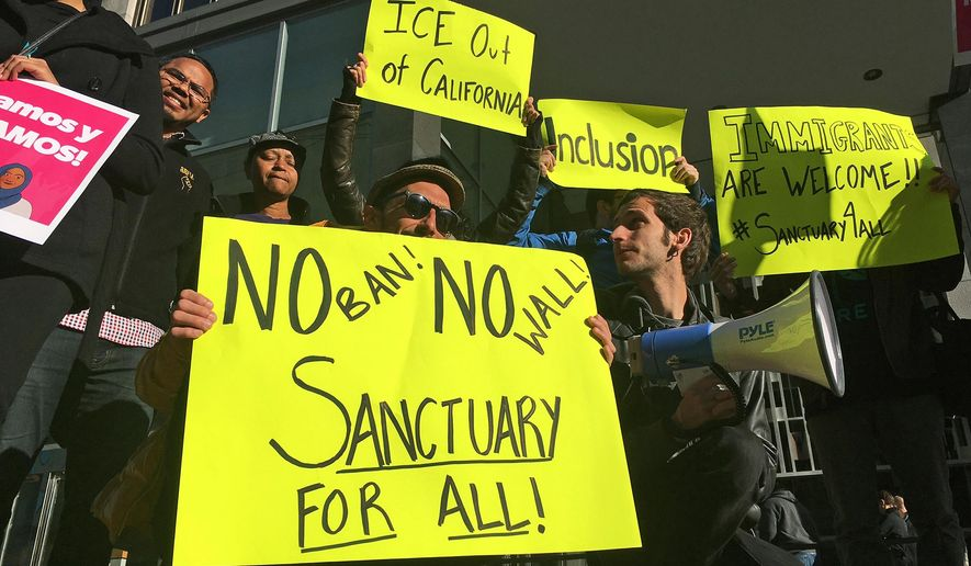 In this April 14, 2017, photo, protesters rally outside a courthouse in San Francisco. U.S. Judge William Orrick struck down an immigration law Friday, Oct. 5, 2018, that the Trump administration has used to go after cities and states that limit cooperation with immigration officials. (AP Photo/Haven Daley) **FILE**