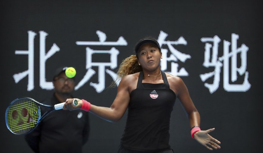 Naomi Osaka of Japan hits a return shot while competing against Zhang Shuai of China in their quarterfinal women's singles match in the China Open at the Lotus Court in Beijing, Friday, Oct. 5, 2018. (AP Photo/Mark Schiefelbein)