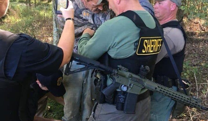 This photo provided by The Tennessee Bureau of Investigation shows law enforcement agents holding Kirby Wallace in custody on Friday, Oct. 5, 2018 in Tennessee. Wallace is wanted on multiple charges after being accused of attacking a couple and setting their house on fire, killing the wife and seriously injuring the husband. He's also accused of fatally shooting a man Monday and stealing his truck.  (The Tennessee Bureau of Investigation via AP)