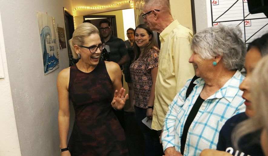 Democratic Rep. Kyrsten Sinema, who is running against Republican Rep. Martha McSally for the open Arizona Senate seat Jeff Flake, R-Ariz., is vacating, talks to campaign volunteers, Tuesday, Oct. 2, 2018, in Tempe, Ariz. Arizona's Senate race pits Sinema, a careful politician running as a centrist in a Republican-leaning state, against McSally, a onetime Trump critic turned fan. (AP Photo/Ross D. Franklin)