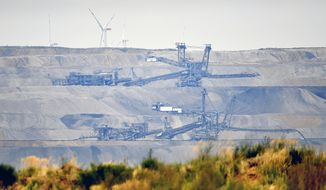 FILE - In this Sept. 7, 2018 file photo bucket wheels dig for coal near the Hambach Forest near Dueren, Germany. On Friday, Oct. 5, 2018 a German court has ordered a temporary halt to plans to fell part of a forest in the west of the country to allow the expansion of a coal mine.  (AP Photo/Martin Meissner, file)