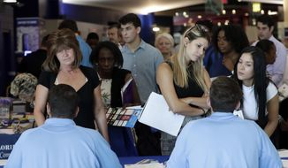 In this June 21, 2018, file photo, job applicants talks with representatives from Aldi at a job fair hosted by Job News South Florida, in Sunrise, Fla. On Friday, Oct. 5, the U.S. government issues the September  jobs report. (AP Photo/Lynne Sladky, File)