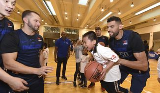 In a photo provided by NBAE, Dallas Mavericks center Salah Mejri, of Tunisia, lifts a participant during the NBA Cares Special Olympics Basketball Clinic, Thursday, Oct. 4, 2018, at Oriental Sports Center in Shanghai. At left is Mavericks guard J.J. Barea. (Randy Belice/NBAE via AP)