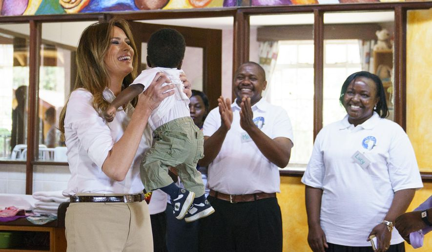 First lady Melania Trump lifts a baby during a visit to the Nest Orphanage in Limuru, Kenya, Friday, Oct. 5, 2018. Mrs. Trump is on her first-ever visit to Africa and her first extended solo international trip as first lady.  (AP Photo/Carolyn Kaster)