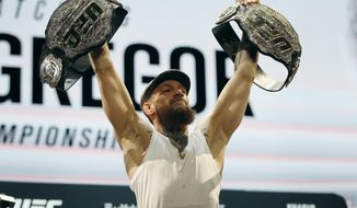 Conor McGregor holds up belts during a news conference for the UFC 229 mixed martial arts bouts Thursday, Oct. 4, 2018, in Las Vegas. McGregor is scheduled to fight Khabib Nurmagomedov on Saturday in Las Vegas. (AP Photo/John Locher)