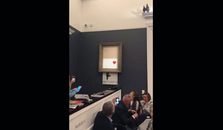 "In this grab taken from video on Friday, Oct. 5, 2018 people watch as the spray-painted canvas ""Girl with Balloon"" by artist Banksy is shredded at Sotheby's, in London, A Banksy artwork self-destructed moments after being sold at auction for 1.04 million pounds ($1.4 million), in a prank apparently orchestrated by the elusive street artist. (Pierre Koukjian via AP)"
