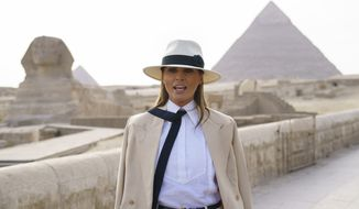 U.S. first lady Melania Trump talks to media as she visits the ancient statue of Sphinx, with the body of a lion and a human head, at the historic Giza Pyramids site near Cairo, Egypt on Saturday, Oct. 6, 2018. Trump is visiting Africa on her first big solo international trip. (AP Photo/Carolyn Kaster)
