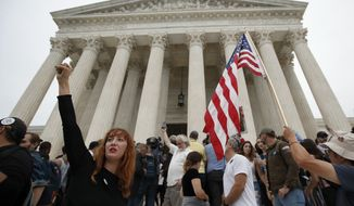 A protester raises her fist as activists protest on the steps of the Supreme Court after the confirmation vote of Supreme Court nominee Brett Kavanaugh, on Capitol Hill, Saturday, Oct. 6, 2018 in Washington. (AP Photo/Alex Brandon)