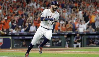 Houston Astros' Marwin Gonzalez (9) races to first base on a hit against the Cleveland Indians during the sixth inning of Game 2 of a baseball American League Division Series, Saturday, Oct. 6, 2018, in Houston. Two runs scored on the play. (AP Photo/David J. Phillip)