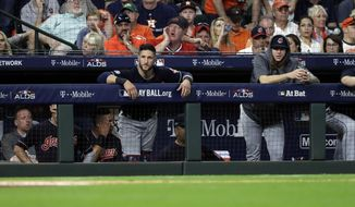 Cleveland Indians players stand in the dugout as they fall to the Houston Astros in Game 2 of a baseball American League Division Series, Saturday, Oct. 6, 2018, in Houston. (AP Photo/David J. Phillip)