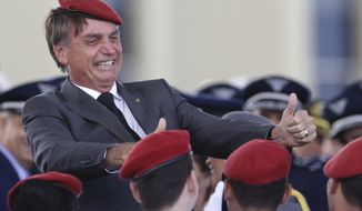 FILE - In this April 19, 2018 file photo, presidential hopeful, conservative Brazilian lawmaker Jair Bolsonaro flashes two thumbs up as he poses for a photo with cadets during a ceremony marking Army Day, in Brasilia, Brazil. For many Brazilians, Bolsonaro's candidacy in Sunday's Oct. 7 vote has long provoked fears because of his penchant for waxing nostalgic about the country's 1964-1985 dictatorship, along with his steady stream of derogatory comments about women, blacks, indigenous peoples and gays. (AP Photo/Eraldo Peres, File)