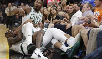 Boston Celtics' Marcus Smart is held back by teammates during a scuffle in the first half of an NBA preseason basketball game against the Cleveland Cavaliers, Saturday, Oct. 6, 2018, in Cleveland. Smart was ejected from the game. (AP Photo/Tony Dejak)