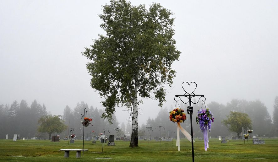 """The early-morning fog shrouds the cemetery in Libby, Montana, on a mid-September day. At least 400 deaths have been documented to be related to asbestos exposure in the town, but health officials suspect the number to be much higher. For years, the hospital was run by W.R. Grace, the same company that owned the mine, and """"asbestos"""" never appeared on a death certificate in Libby. (Kurt Wilson/The Missoulian via AP)"""