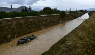 A car in a stream after a storm hit the town of Argos, southwest of Athens, on Sunday, Sept. 30, 2018. Greek authorities are looking for three missing people on a Greek island after a rare and powerful Mediterranean storm dumped heavy rain on the region. (AP Photo/Vangelis Bougiotis)