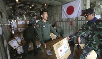 Indonesian and Japan military personnel unload relief aid from a Japan Air Force cargo plane at the Mutiara Sis Al-Jufri airport in Palu, Central Sulawesi, Indonesia, Saturday, Oct. 6, 2018. As the sun slipped behind the mountains and a gentle breeze blew onshore, hundreds of people gathered on an Indonesian beach Friday to chant a Muslim prayer and remember those they lost one week after a massive earthquake and tsunami ravaged the area, killing more than 1,500 people.(AP Photo/Tatan Syuflana)
