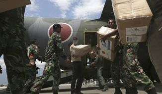 Indonesian and Japan military personnel unload relief aid from a Japan Air Force cargo plane at the Mutiara Sis Al-Jufri airport in Palu, Central Sulawesi, Indonesia, Saturday, Oct. 6, 2018.  A 7.5 magnitude earthquake rocked the city on Sept. 28, triggering a tsunami and mud slides that killed a large number of people and displaced tens of thousands others. (AP Photo/Tatan Syuflana)