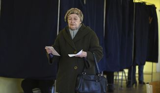 A Latvian woman holds her ballot papers at a polling station in Riga, Latvia, Saturday, Oct. 6, 2018. Latvians were casting their ballots on Saturday in a parliamentary election in which a party catering to the Baltic nation's large ethnic-Russian minority is expected to win the most votes, but is seen to be struggling to find coalition partners. (AP Photo/Roman Koksarov)