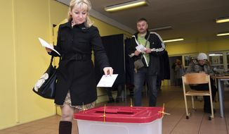 A Latvian woman casts her ballot papers at a polling station in Riga, Latvia, Saturday, Oct. 6, 2018. Latvians were casting their ballots on Saturday in a parliamentary election in which a party catering to the Baltic nation's large ethnic-Russian minority is expected to win the most votes, but is seen to be struggling to find coalition partners. (AP Photo/Roman Koksarov)