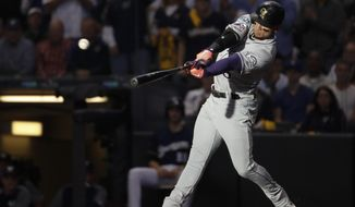 Colorado Rockies' Carlos Gonzalez hits a triple during the fifth inning of Game 1 of the National League Divisional Series baseball game against the Milwaukee Brewers Thursday, Oct. 4, 2018, in Milwaukee. (AP Photo/Jeff Roberson)