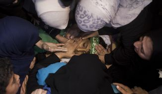 Relatives of 12-year-old Palestinian boy, Fares Sersawi, who was killed by Israeli troops on Friday's protest at the Gaza Strip's border with Israel, mourn over his body at the family home during his funeral in Gaza City, Saturday, Oct. 6, 2018. (AP Photo/Khalil Hamra)