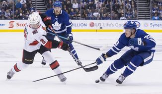 Ottawa Senators' Dylan DeMelo (2) gets a shot away as Toronto Maple Leafs' Travis Dermott (23) closes in during first period NHL hockey action in Toronto on Saturday, Oct. 6, 2018. (Chris Young/The Canadian Press via AP)