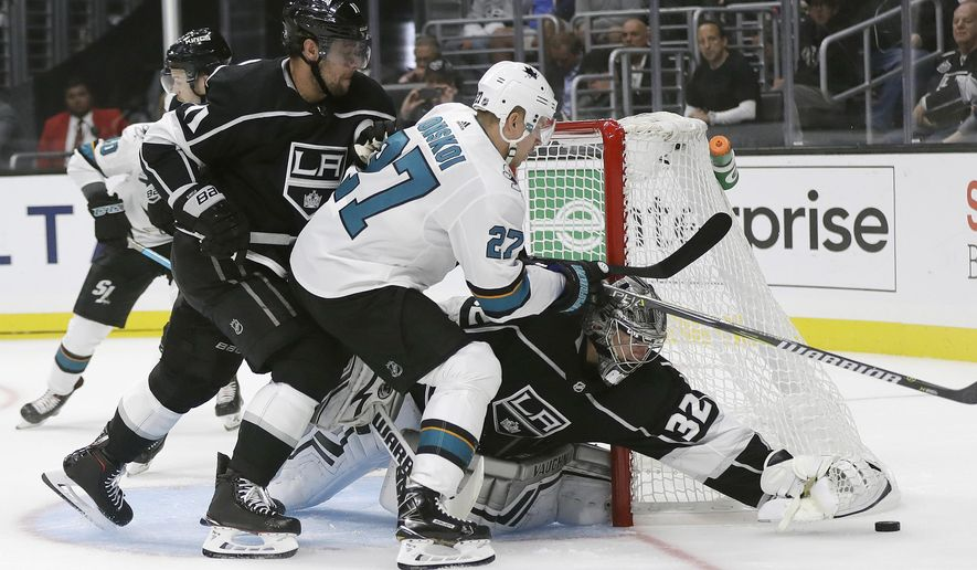 Los Angeles Kings' Jonathan Quick, right, stops a shot next to San Jose Sharks' Joonas Donskoi (27) during the first period of an NHL hockey game Friday, Oct. 5, 2018, in Los Angeles. (AP Photo/Marcio Jose Sanchez)