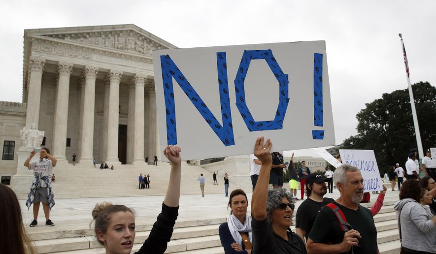 Activists demonstrate in front of the Supreme Court to protest the confirmation vote of Supreme Court nominee Brett Kavanaugh on Capitol Hill, Saturday, Oct. 6, 2018 in Washington. (AP Photo/Alex Brandon)