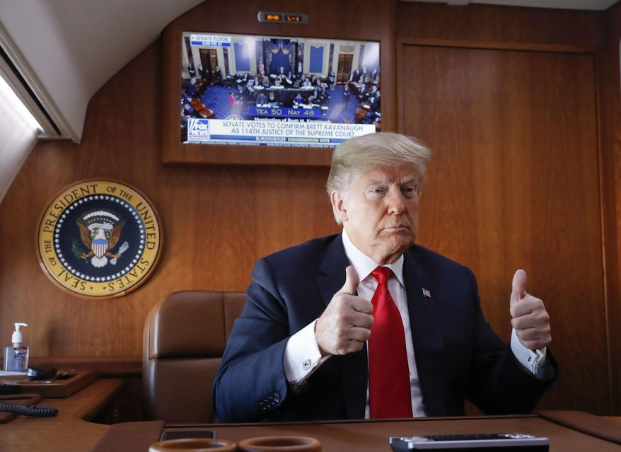 President Donald Trump, on board Air Force One, gives a 'thumbs-up' while watching a live television broadcast of the Senate confirmation vote of Supreme Court nominee Brett Kavanaugh, Saturday, Oct. 6, 2018. Trump was traveling from Washington enroute to Topeka, Kan., for a campaign rally. (AP Photo/Pablo Martinez Monsivais)