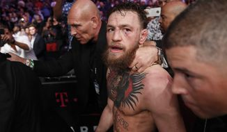 Conor McGregor is escorted from the cage area after fighting Khabib Nurmagomedov in a lightweight title mixed martial arts bout at UFC 229 in Las Vegas, Saturday, Oct. 6, 2018. Nurmagomedov won the fight by submission during the fourth round to retain the title. (AP Photo/John Locher) ** FILE **