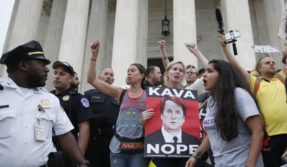 Police move activists as they protest on the steps of the Supreme Court after the confirmation vote of Supreme Court nominee Brett Kavanaugh, on Capitol Hill, Saturday, Oct. 6, 2018 in Washington. (AP Photo/Alex Brandon) **FILE**