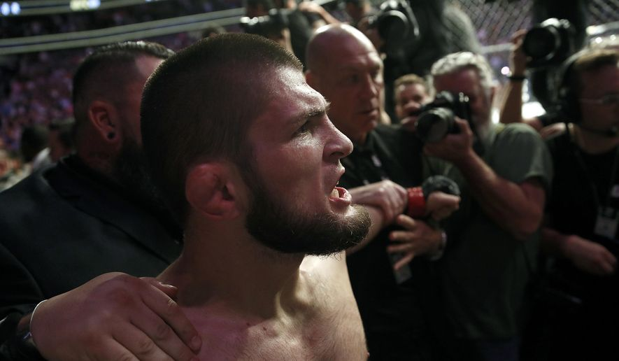 Khabib Nurmagomedov is held back outside of the cage after beating Conor McGregor in a lightweight title mixed martial arts bout at UFC 229 in Las Vegas, Saturday, Oct. 6, 2018. Nurmagomedov won the fight by submission during the fourth round to retain the title. (AP Photo/John Locher) **FILE**