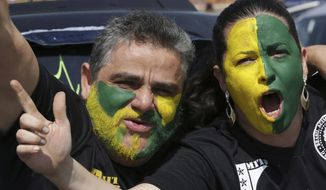 With the faces painted with the colors of Brazil, demonstrators shout slogans during a race in support of Jair Bolsonaro, presidential candidate for the National Social Liberal Party, in the center of Brasilia, Brazil, Saturday, Oct. 6, 2018. Brazil will hold general elections on Oct. 7. (AP Photo/Eraldo Peres)