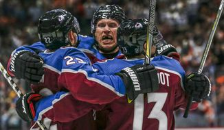 Colorado Avalanche defenseman Erik Johnson, center, hugs center Colin Wilson, left, and forward Alexander Kerfoot (13) after Wilson's goal against the Philadelphia Flyers during the first period of an NHL hockey game Saturday, Oct. 6, 2018, in Denver.(AP Photo/Joe Mahoney)