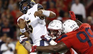 Arizona linebacker Colin Schooler (7) and defensive tackle Dereck Boles (99) tackle California quarterback Brandon McIlwain (5) during the first half of an NCAA college football game Saturday, Oct. 6, 2018, in Tucson, Ariz. (AP Photo/Chris Coduto)