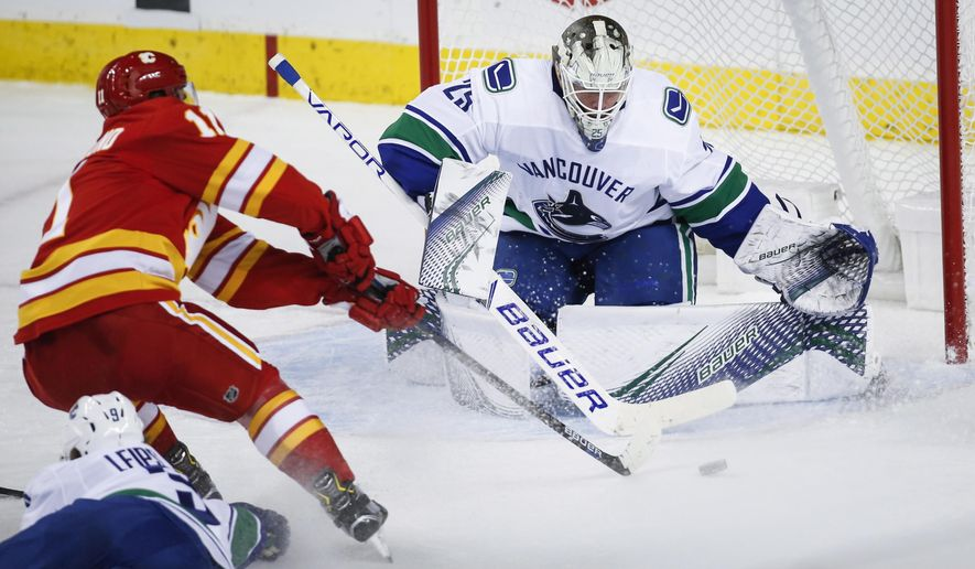 Vancouver Canucks goalie Jacob Markstrom, right, of Sweden, blocks the net on Calgary Flames' Mikael Backlund, of Sweden, during the second period of an NHL hockey game in Calgary, Alberta, Saturday, Oct. 6, 2018. (Jeff McIntosh/The Canadian Press via AP)