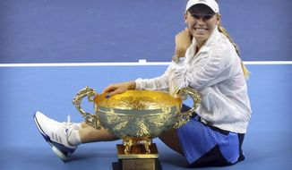 Caroline Wozniacki of Denmark poses with the winner's trophy after beating Anastasija Sevastova of Latvia in the women's singles final in the China Open at the National Tennis Center in Beijing, Sunday, Oct. 7, 2018. (AP Photo/Mark Schiefelbein)