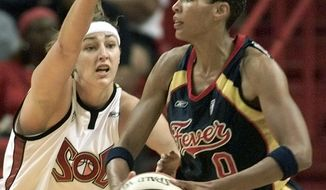 FILE - In this June 30, 2002, file photo, Indiana Fever center Olympia Scott-Richardson (0) looks for an open teammate as Miami Sol center Ruth Riley (7) defends in the first half in Miami. Riley Hunter's WNBA career started in Miami, and so will her NBA career. She will debut in her new role as a radio and television analyst for the Miami Heat on Monday, Oct. 8, 2018, when the team begins the home portion of its preseason schedule against Orlando. (AP Photo/Wilfredo Lee, File)