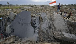 """A sign """"Pray for Petobo"""" is placed on a piece of a road on Saturday Oct. 6, 2018 after it moved when earthquake hit Petobo neighborhood in Palu, Central Sulawesi, Indonesia last week. Search teams pulled bodies from obliterated neighborhoods in the disaster-stricken Indonesian city of Palu on Saturday as more aid rolled in and the government said it was considering making devastated areas into mass graves. (AP Photo/Aaron Favila)"""