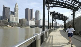 In this March 15, 2004, file photo, a woman runs the Franklinton floodwall next to the Scioto River in Columbus, Ohio. The largest city named for Christopher Columbus has called off its observance of the holiday named for the explorer. Offices in Columbus, Ohio, will remain open Monday, Oct. 8, 2018, and close on Veterans Day instead. (AP Photo/Jay LaPrete, File)