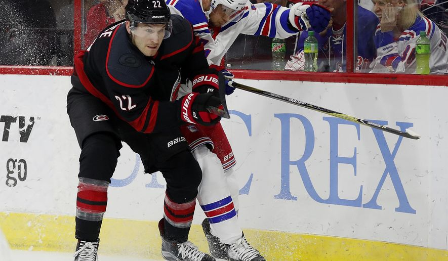 Carolina Hurricanes' Brett Pesce (22) battles New York Rangers' Ryan Spooner (23) for the puck during the first period of an NHL hockey game, Sunday, Oct. 7, 2018, in Raleigh, N.C. (AP Photo/Karl B DeBlaker)