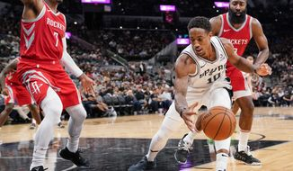San Antonio Spurs' DeMar DeRozan (10) tangles with Houston Rockets' Carmelo Anthony (7) and James Harden during the second half of an NBA preseason basketball game, Sunday, Oct. 7, 2018, in San Antonio. (AP Photo/Darren Abate)