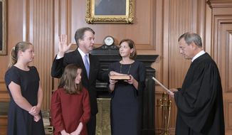 Chief Justice John Roberts, right, administers the Constitutional Oath to Judge Brett Kavanaugh in the Justices' Conference Room of the Supreme Court Building. Ashley Kavanaugh holds the Bible. In the foreground are their daughters, Margaret, left, and Liza. (Fred Schilling/Collection of the Supreme Court of the United States via AP)